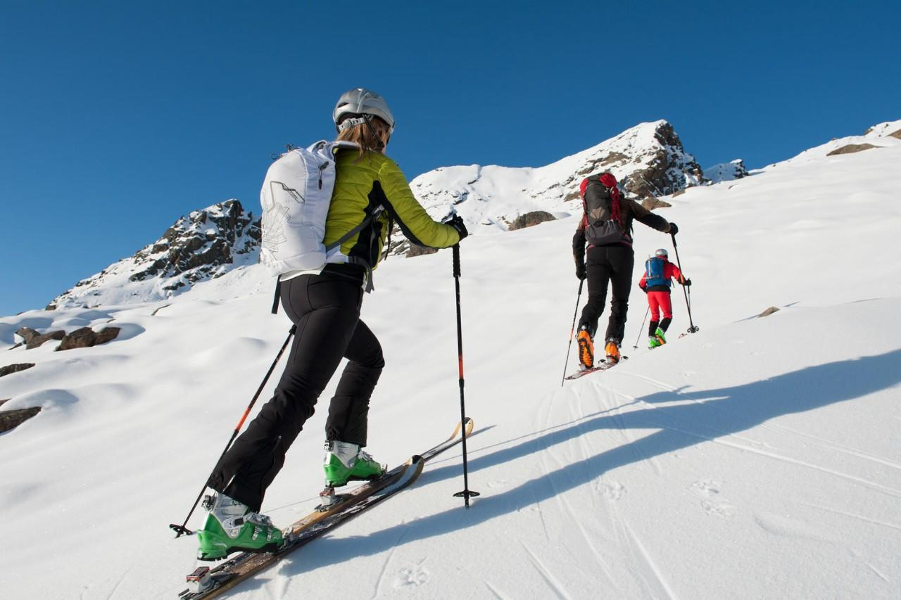 Ski touring hiking uphill in the mountains.