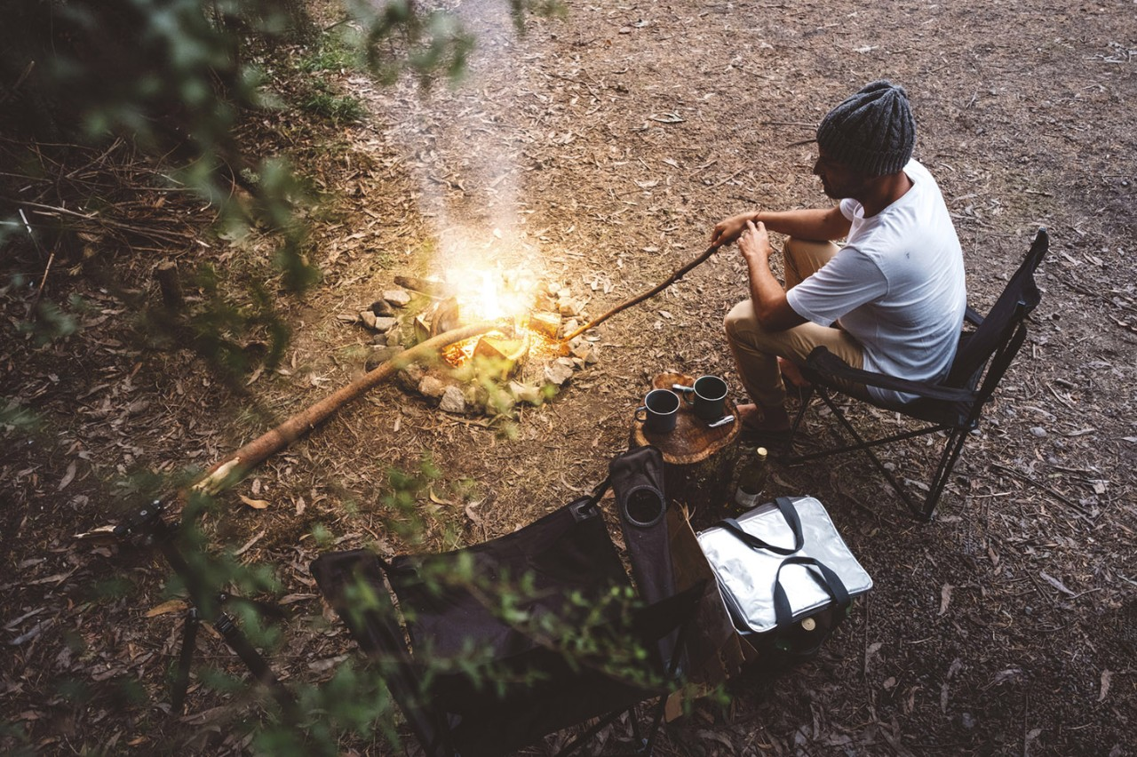 High angle view of hiker sitting on camping chair by campfire in forest