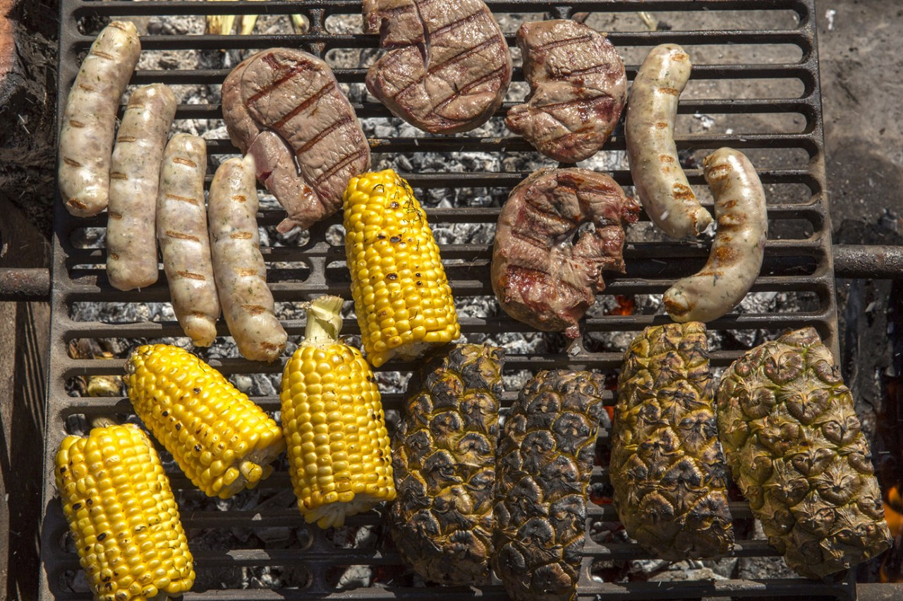 Overhead view of meats, pineapple and corn on grill above campfire
