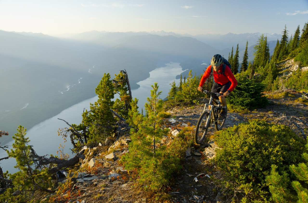 A mountain biker rides high above Kootenay Lake in the Purcell Mountains of British Columbia