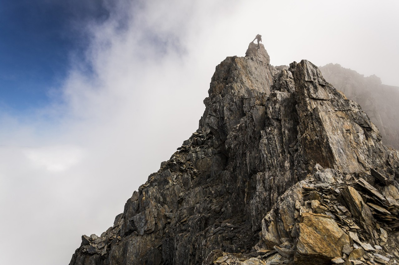 Low angle view of man climbing on mountain