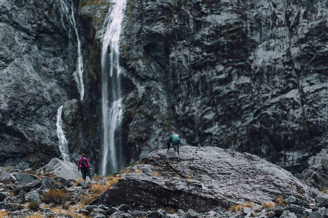 An athletic couple climbs to the basin of a waterfall